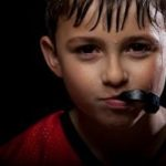 Young buy with a custom mouth guard, provided by his Tulsa dentist, in his mouth getting ready for his football game.