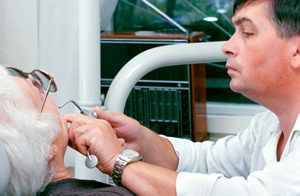 Tulsa dentist examining an elderly patient before dental implant placement procedure at T-Town Smiles.